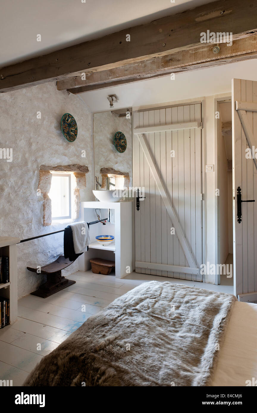 Stone Walled Bedroom With Wooden Beamed Ceiling, Washstand And Fur Throw On  Bed   Stock