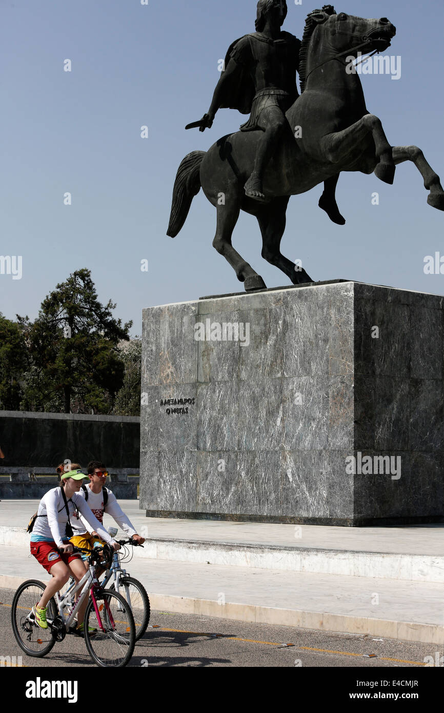 A couple bicycling in front of Alexander the Great statue in Thessaloniki, Greece - Stock Image