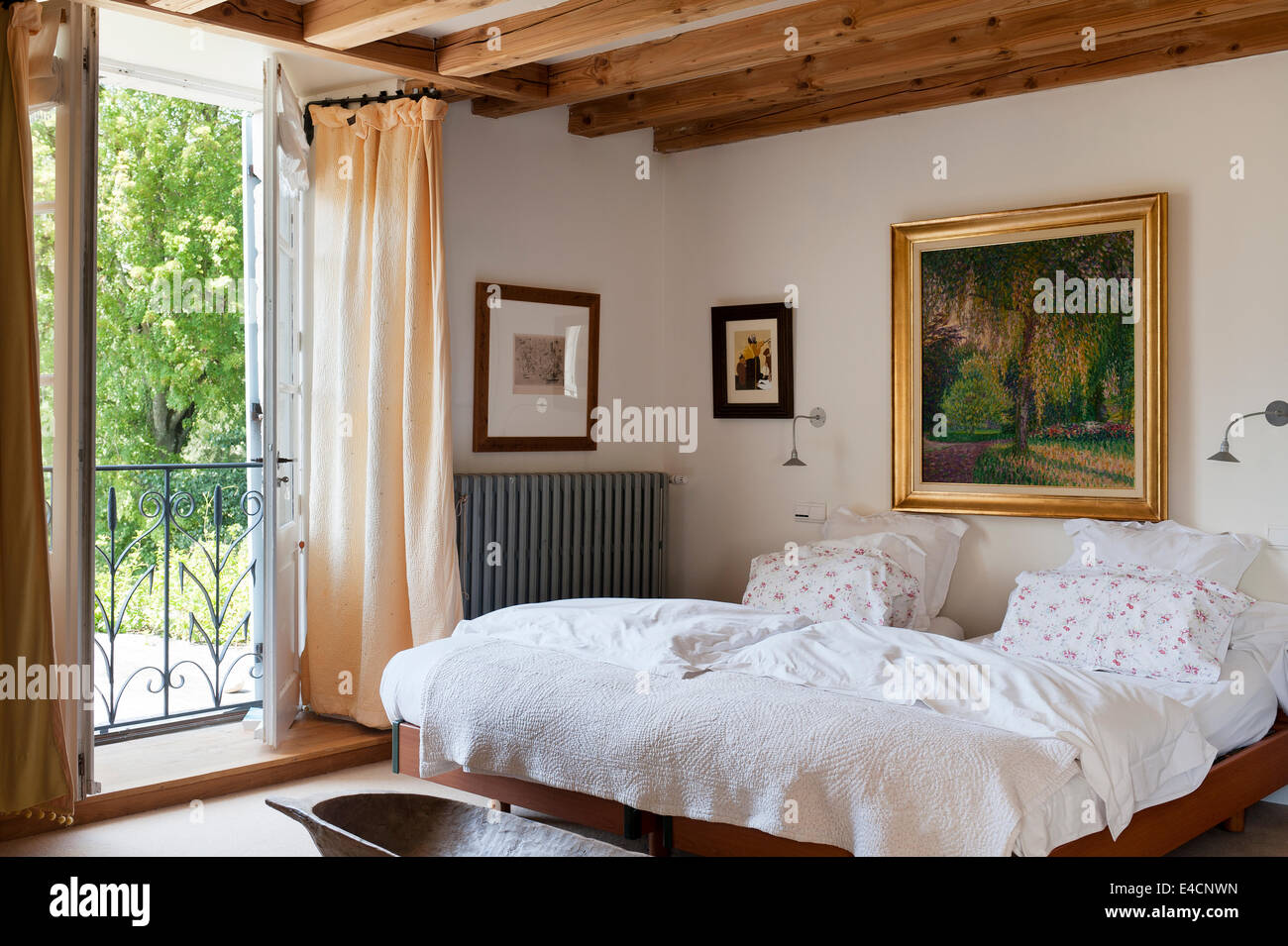 Gilt framed landscape painting on the wall of a bedroom with wooden ...
