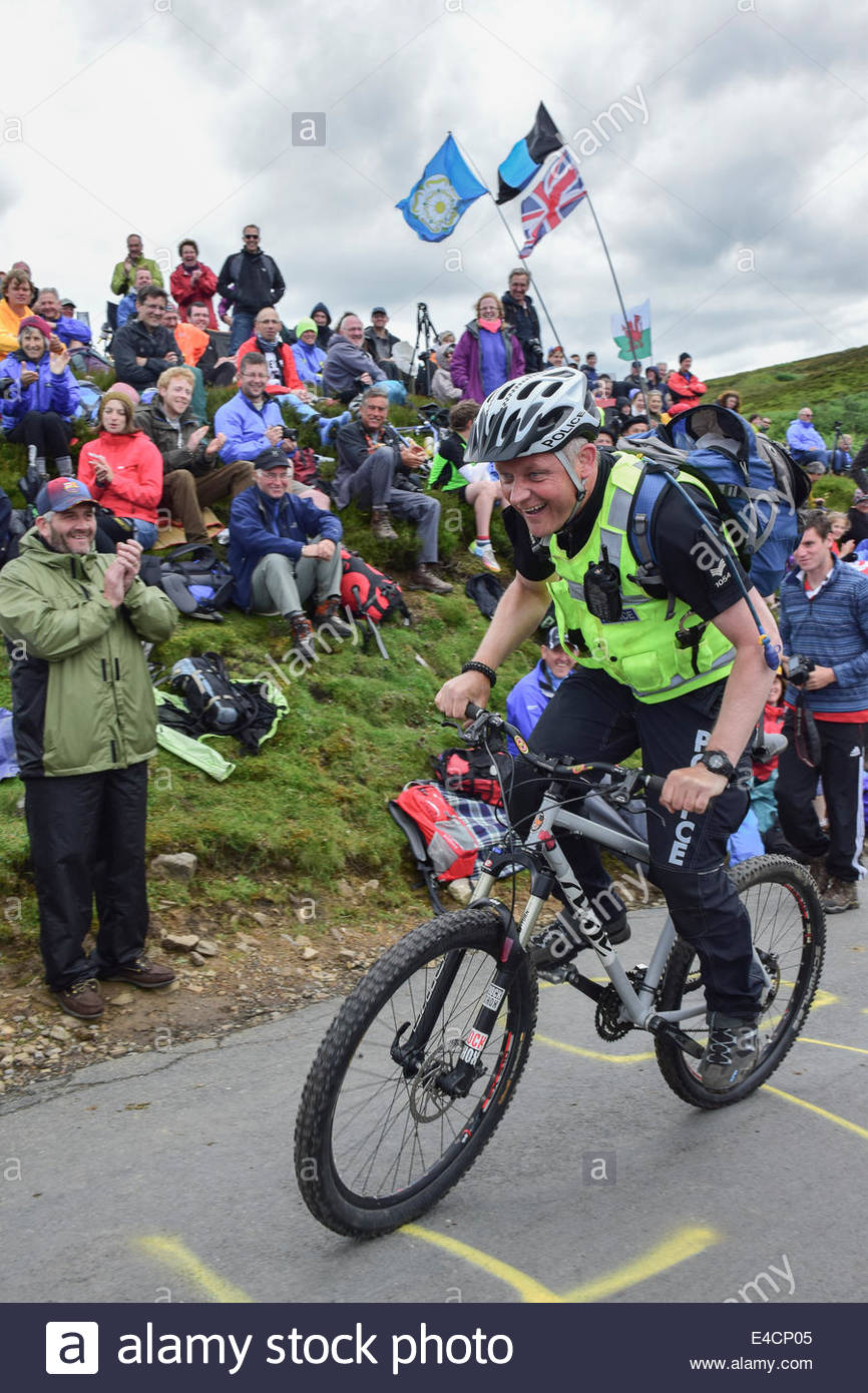 A policeman tackles a climb on his mountain bike to cheers from spectators on Stage 1 of the Tour de France on Grinton - Stock Image