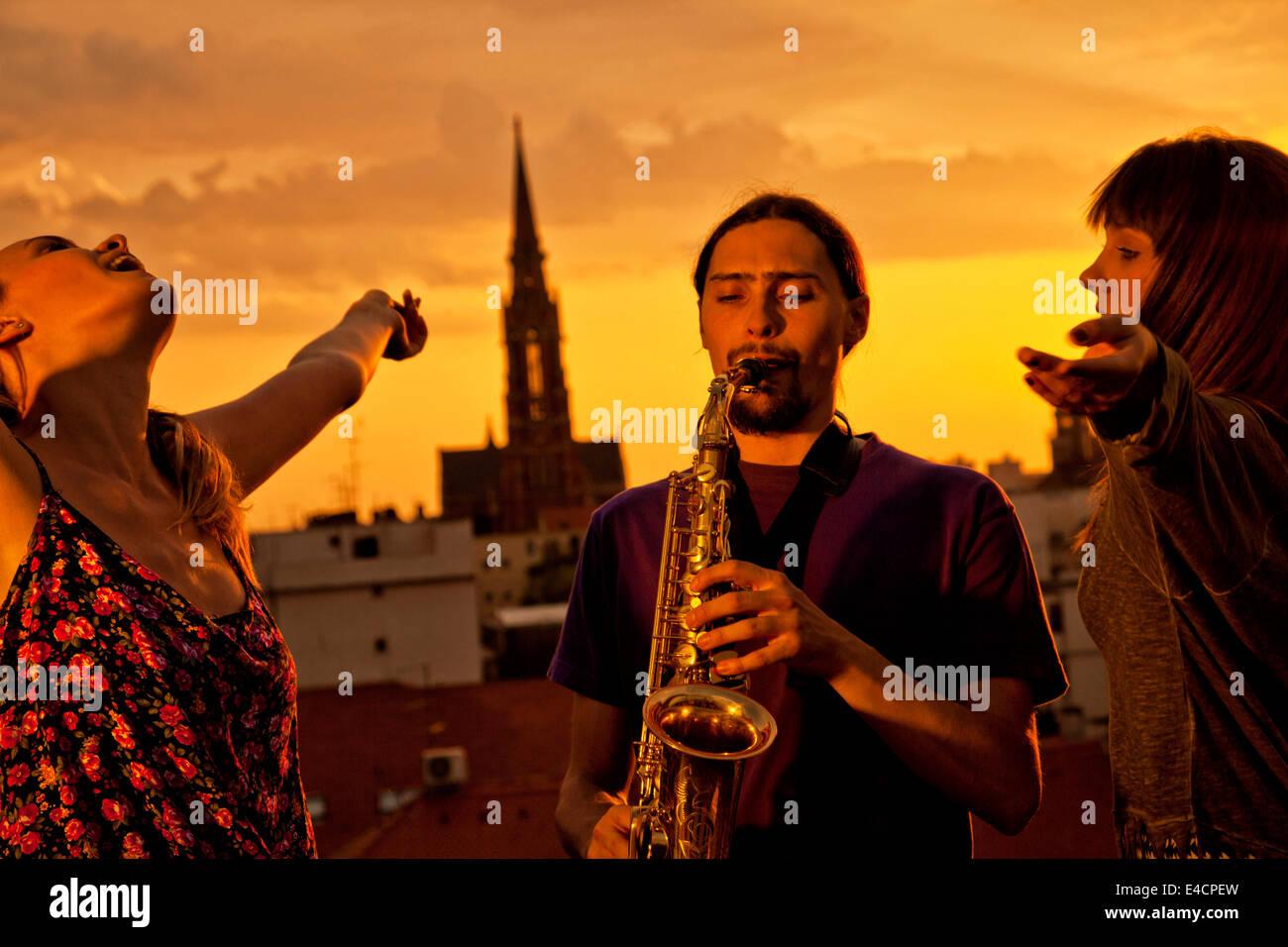 Young man playing the saxophone at sunset, Osijek, Croatia - Stock Image