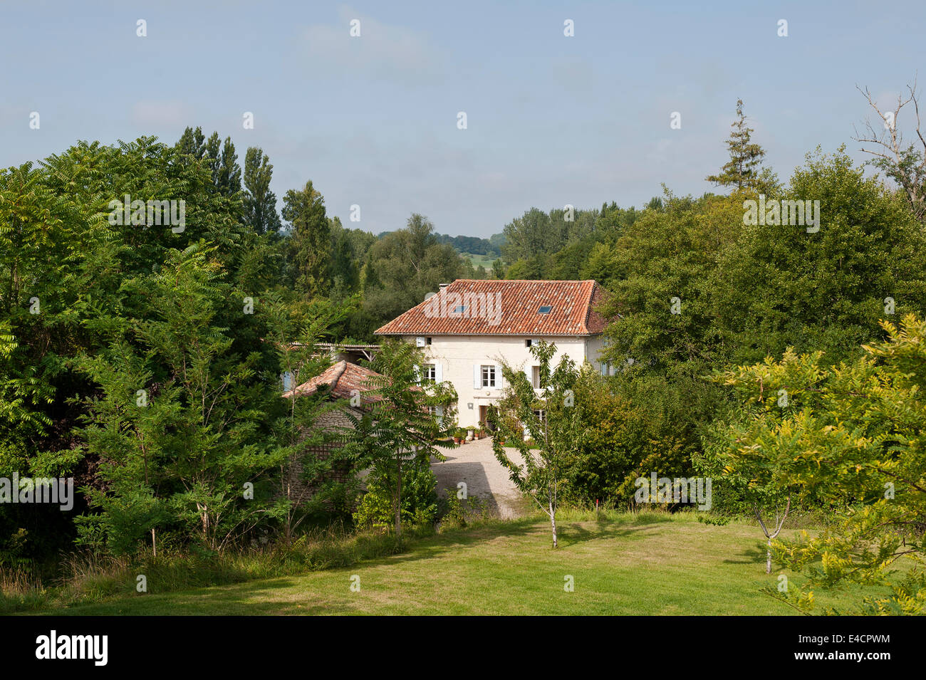 Exterior facade of the converted mill surrounded by green leaved trees - Stock Image