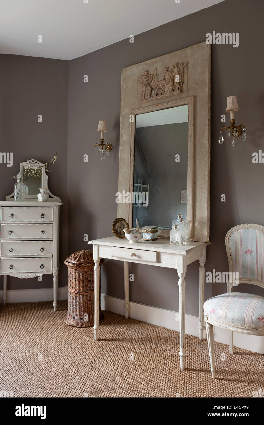 Mirror with plaster cast frame on antique wooden table in bathroom with seagrass carpet Stock Photo