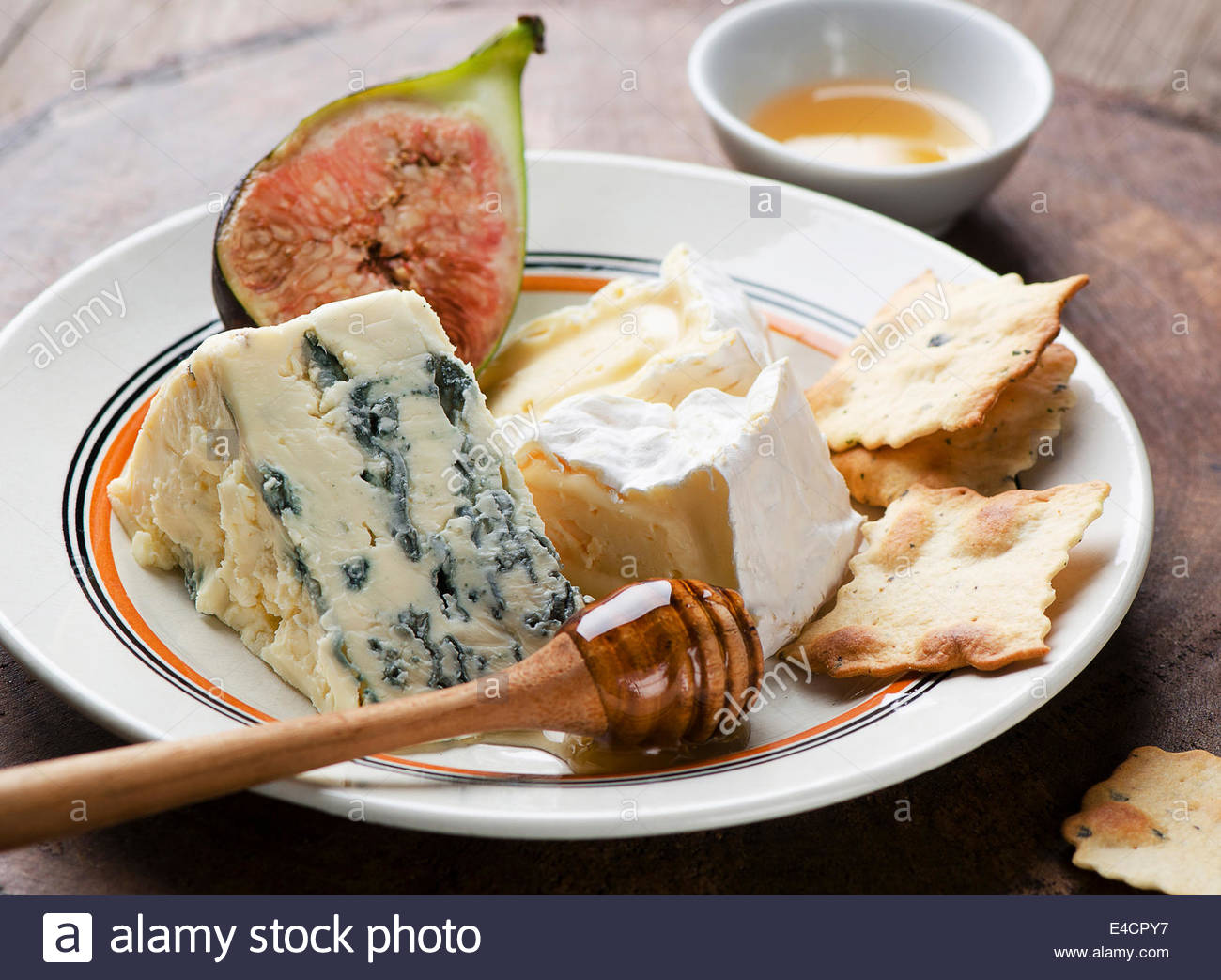 Assortment of fresh cheeses and honey with fig and crackers - Stock Image