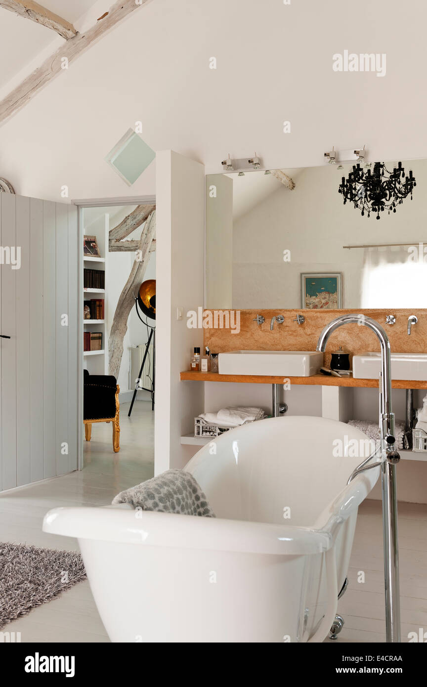 Freestanding bath in room with pair of belfast style sinks - Stock Image