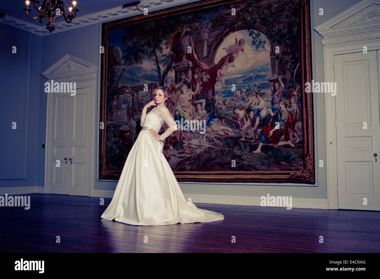 Bride stands with hand on hip against huge painting, Dorset, England - Stock Image