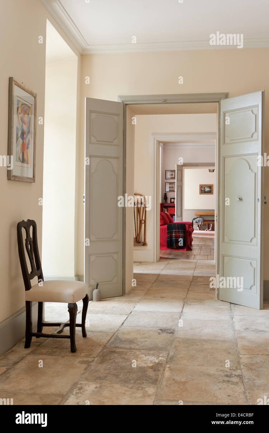 French antique dining chair in stone floored hallway - Stock Image