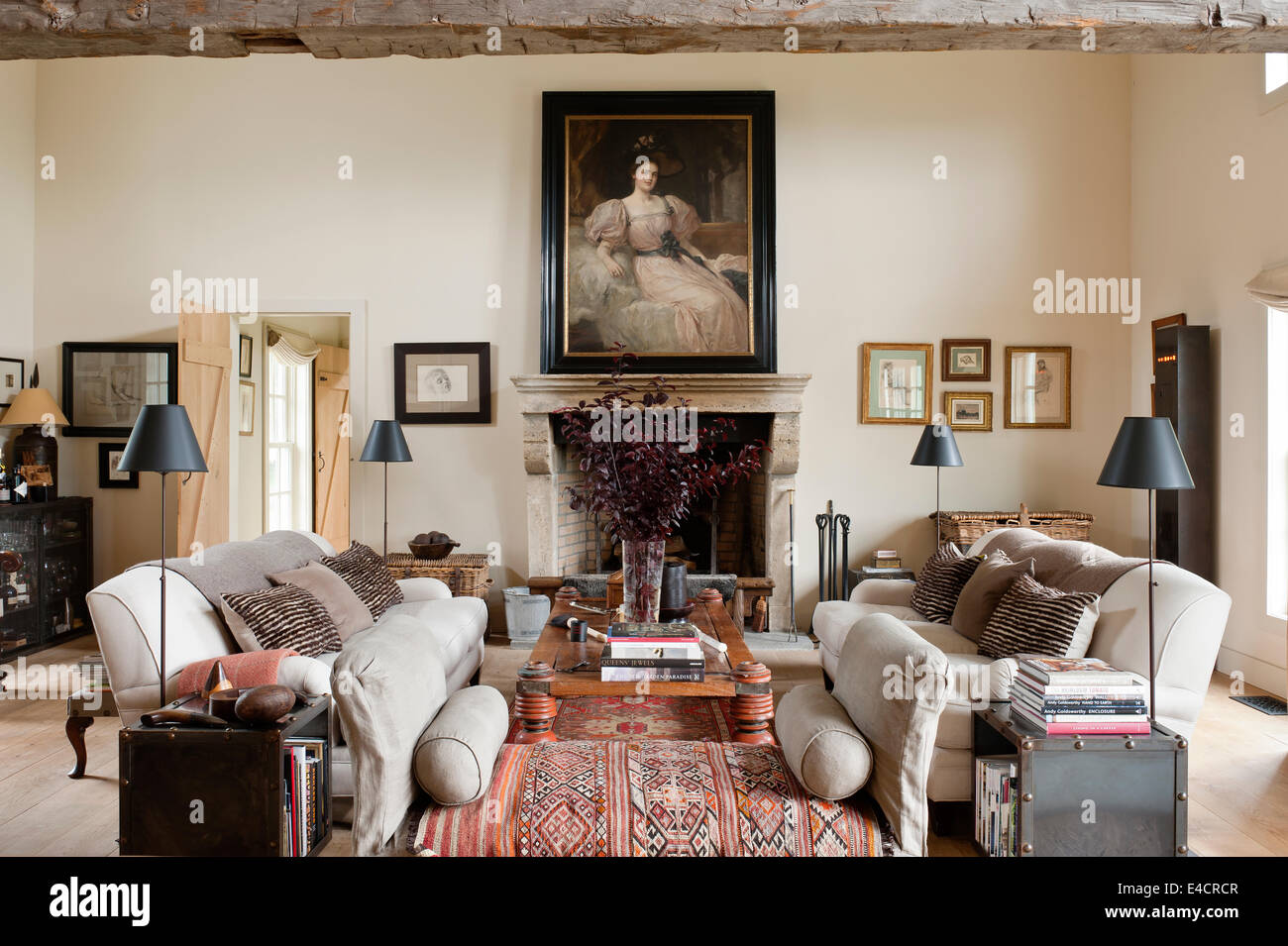 Heavy Danish linen upholstered sofas in living room with old oriental carpets. The black floor lamps are by Madura - Stock Image