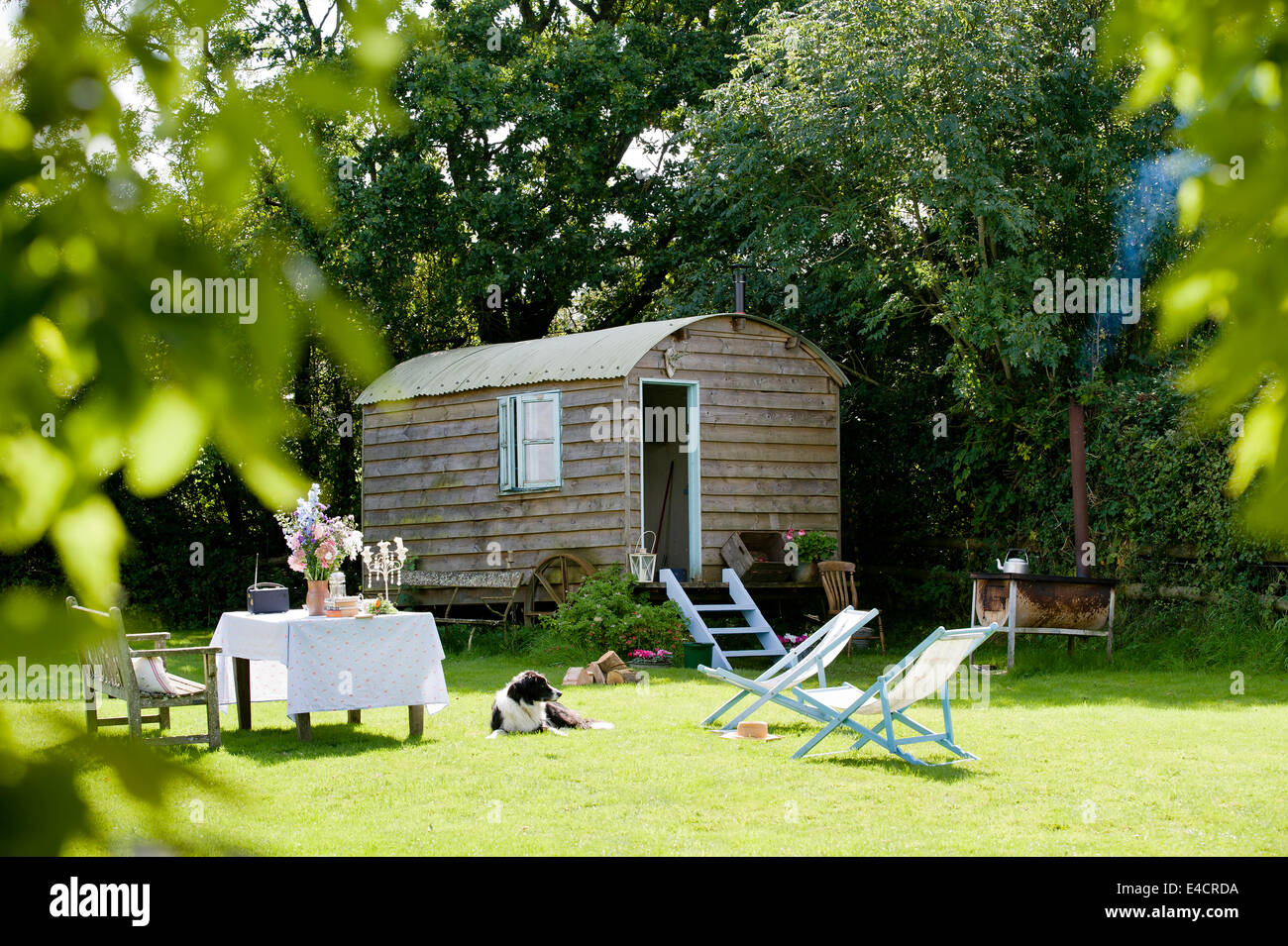 A homemade shepherds hut in an English country garden with deckchairs - Stock Image