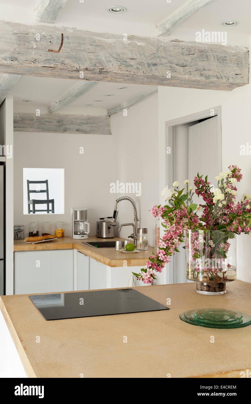 Vase of flowers on yellow sand coloured concrete work surfaces in kitchen with ceiling beamd Stock Photo