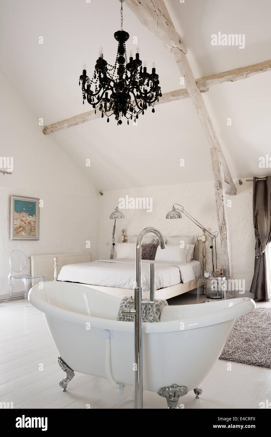 Freestanding bath in large bedroom with black chandelier and ceiling ...