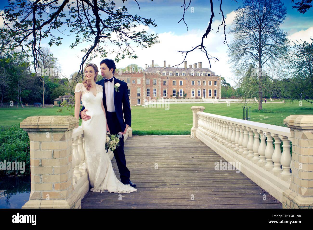 Wedding preparations, Bride and bridegroom on bridge in park, Dorset, England - Stock Image