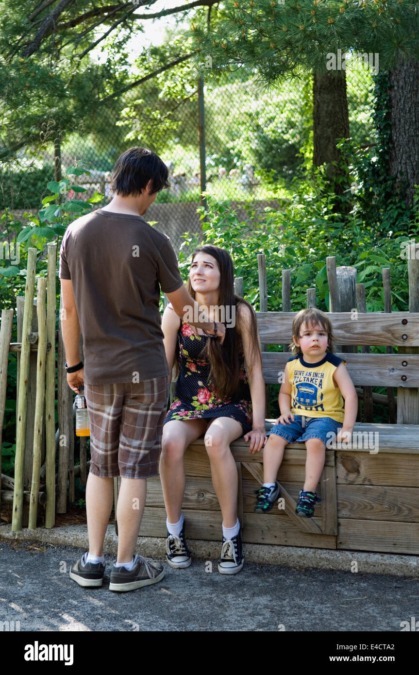 Young Family Resting on Bench at the Louisville Zoo in Kentucky - Stock Image
