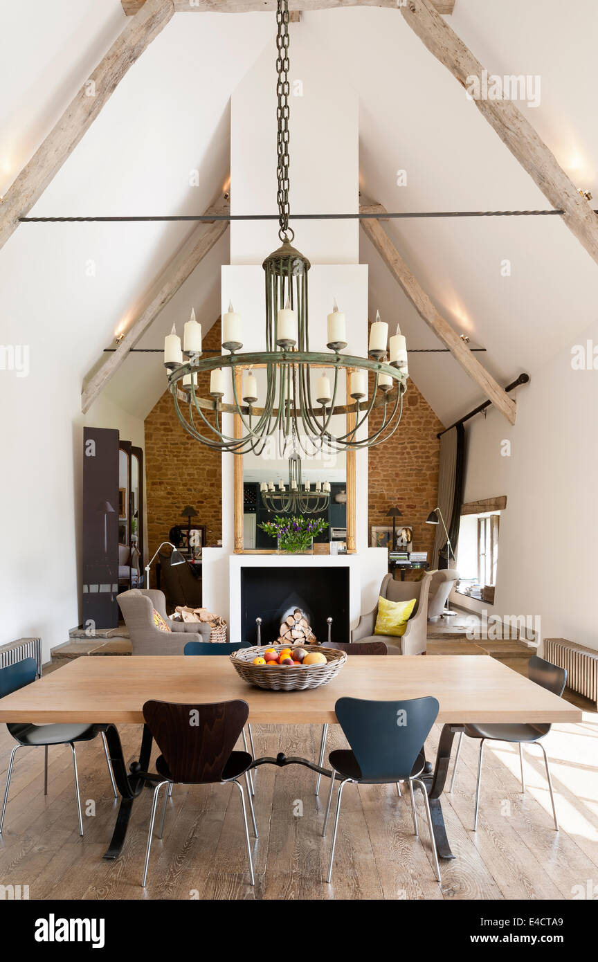 Verdigris chandelier hangs above an oak topped dining table in open plan living space with fireplace acting as partition. - Stock Image