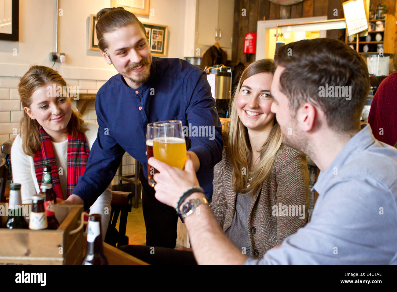 Young men toasting with beer in pub, Bournemouth, Dorset, England - Stock Image