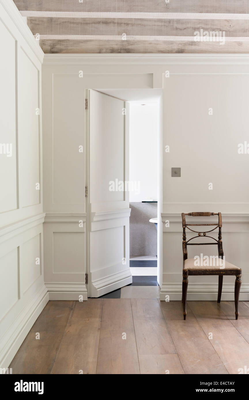 William IV style chair by concealed door in room with white wall panelling, wooden floorboards and ceiling beams - Stock Image