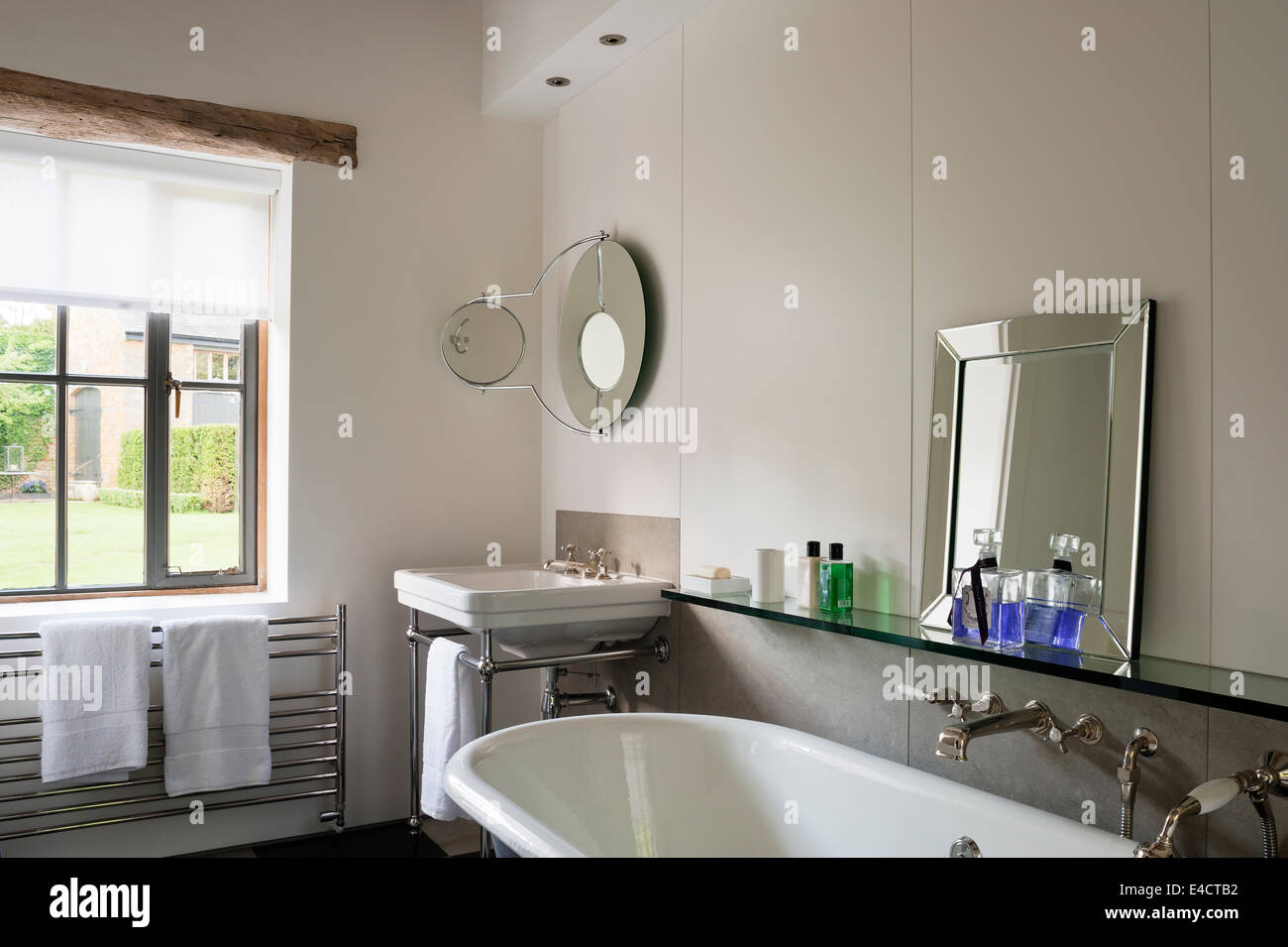 Roll top bath in white bathroom with glass shelf and mirrors - Stock Image
