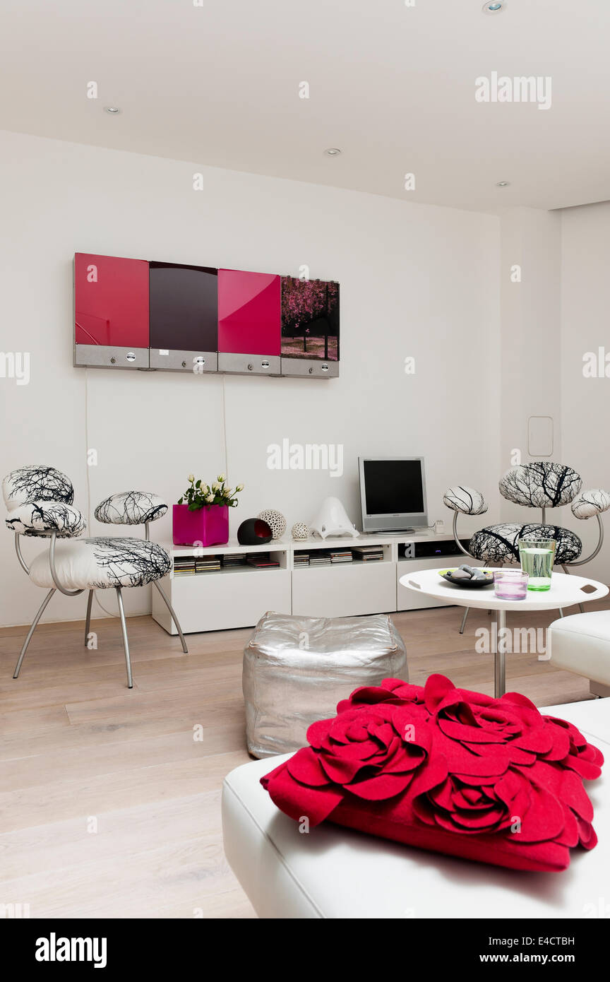 Red cushion from John Lewis on white modular Edra sofa in living room with silver floor cushion Stock Photo