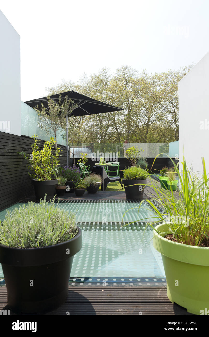 Outdoor furniture and potted plants on modern roof terrace - Stock Image