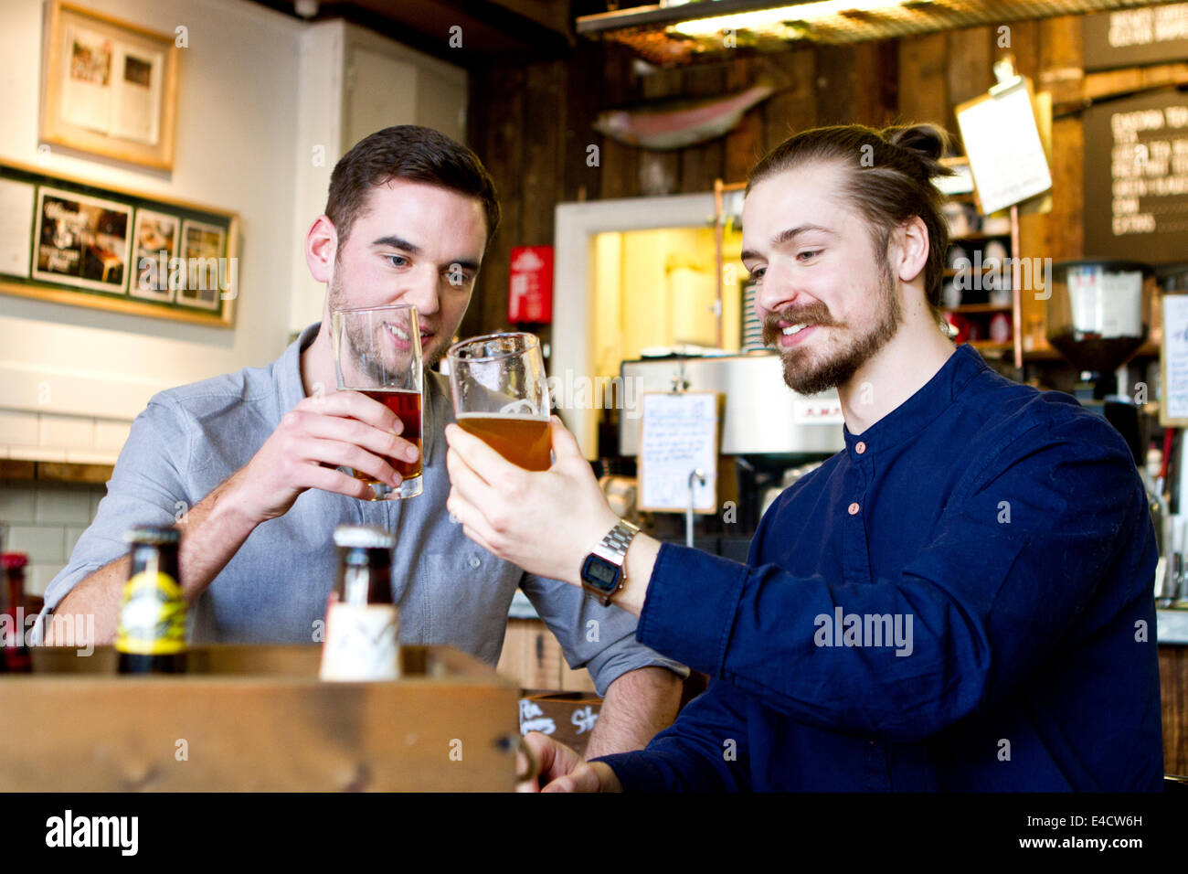 Young men toasting with beer in pub, Dorset, Bournemouth, England - Stock Image