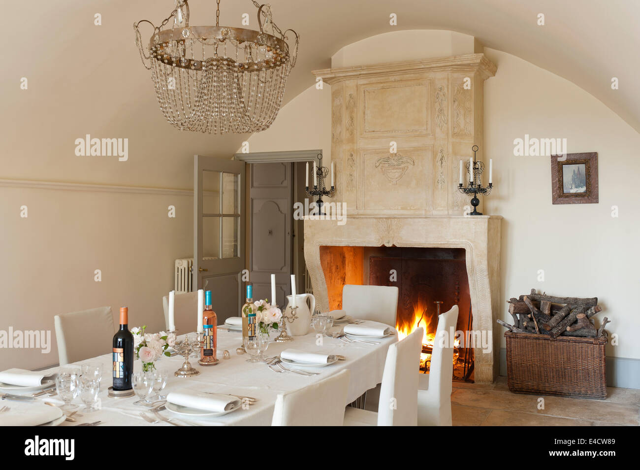 Large Open Stone Fireplace In Vaulted Dining Room With 19th Century Crystal Light And Candelabra French Linen Table Cloth C