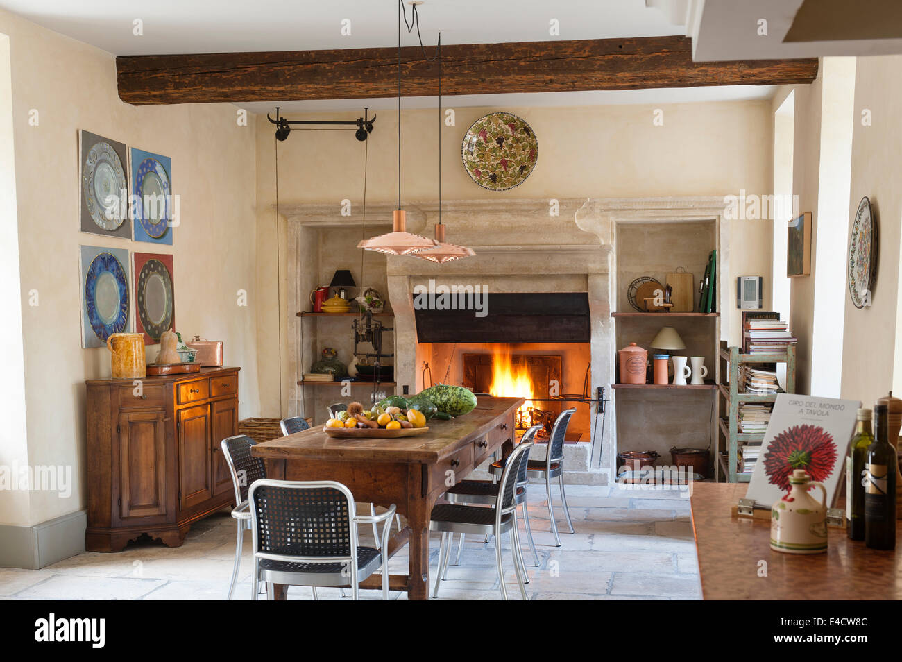 Provencal Kitchen With Large Stone Fireplace And Wooden Dining Table The Copper Pendant Lights Are An Arne Jacobsen Design