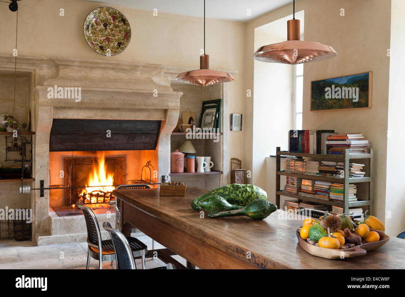 Provencal kitchen with large stone fireplace and wooden dining table. The copper pendant lights are an Arne Jacobsen Stock Photo