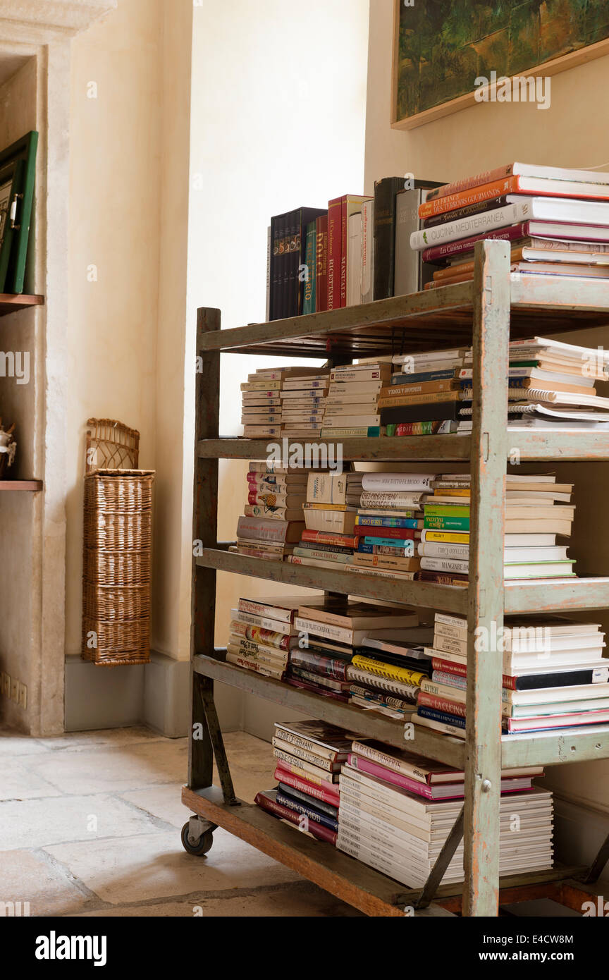 Piles of books on a wooden shelf trolley with distressed paintwork - Stock Image
