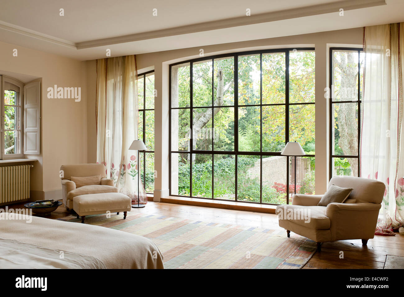 Large window with garden views in bedroom with low armchairs ...