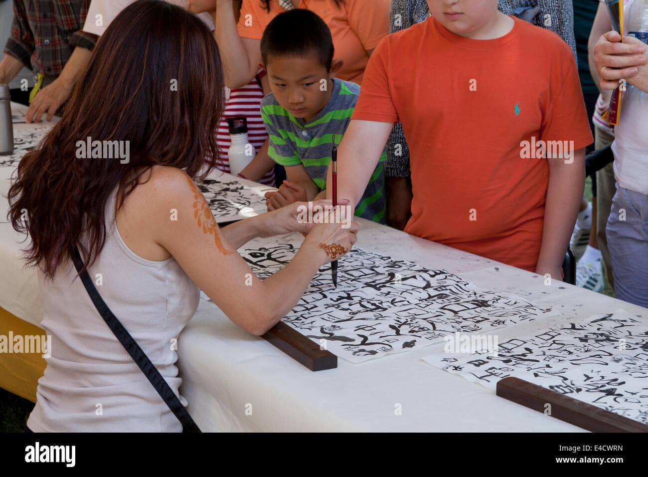 Woman teaching boy Chinese calligraphy - Stock Image