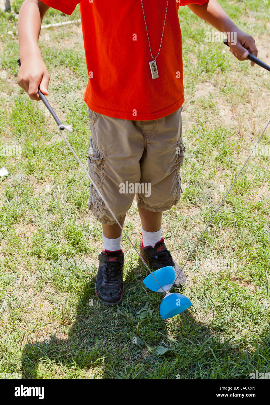Child playing with diabolo juggling toy - USA - Stock Image