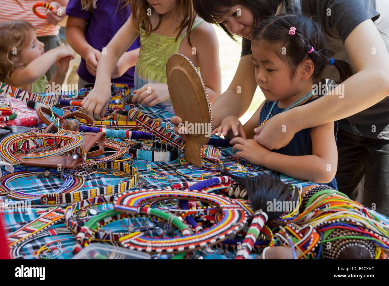 Child trying on Kenyan tassel jewelry - USA - Stock Image