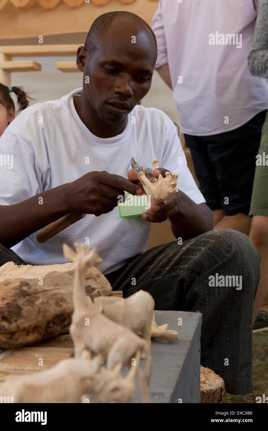 Kenyan man making animal wood carving - USA - Stock Image