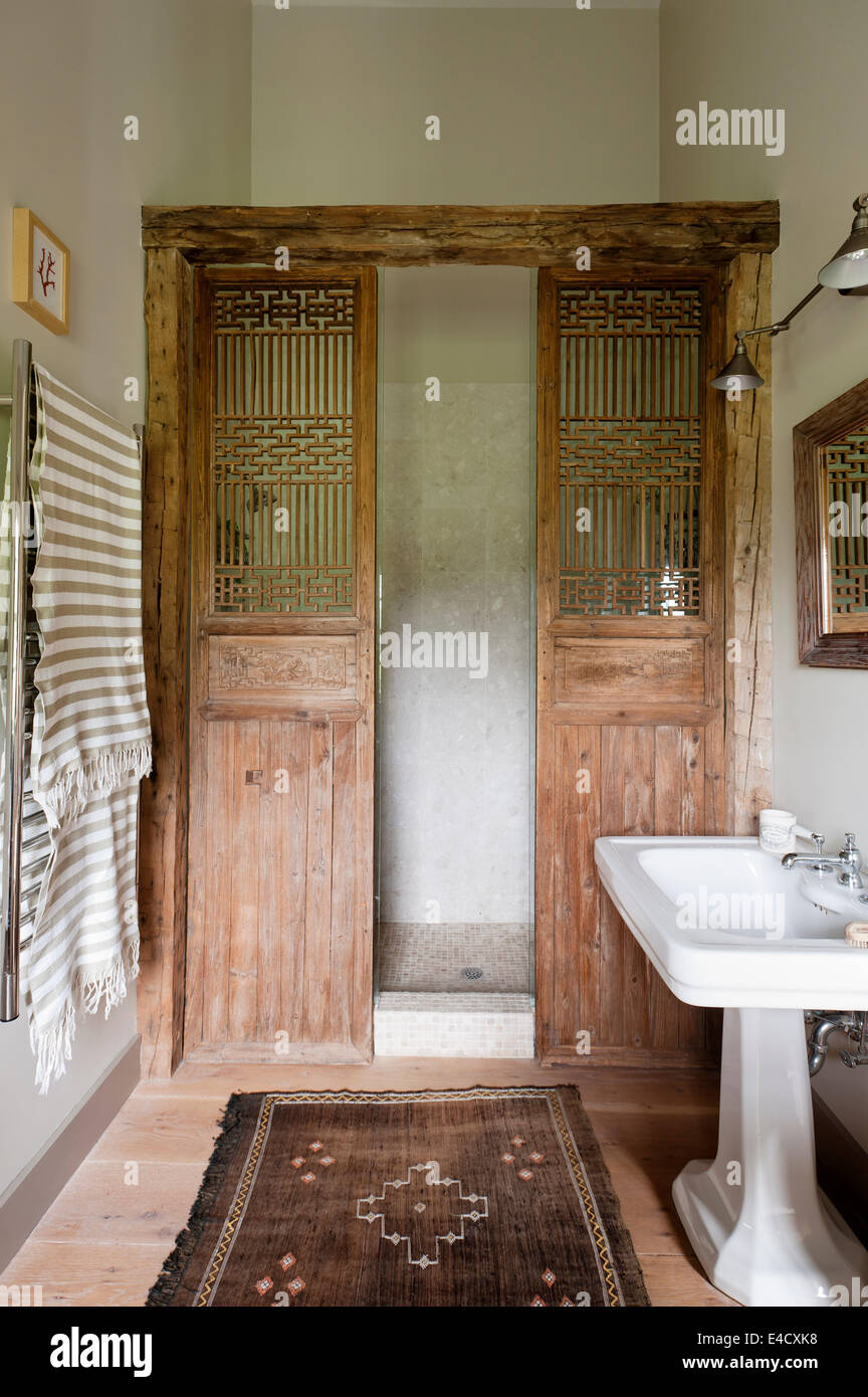 A pair of old chinese wooden doors used as a shower screen in bathroom with Aston Matthews handbasin - Stock Image