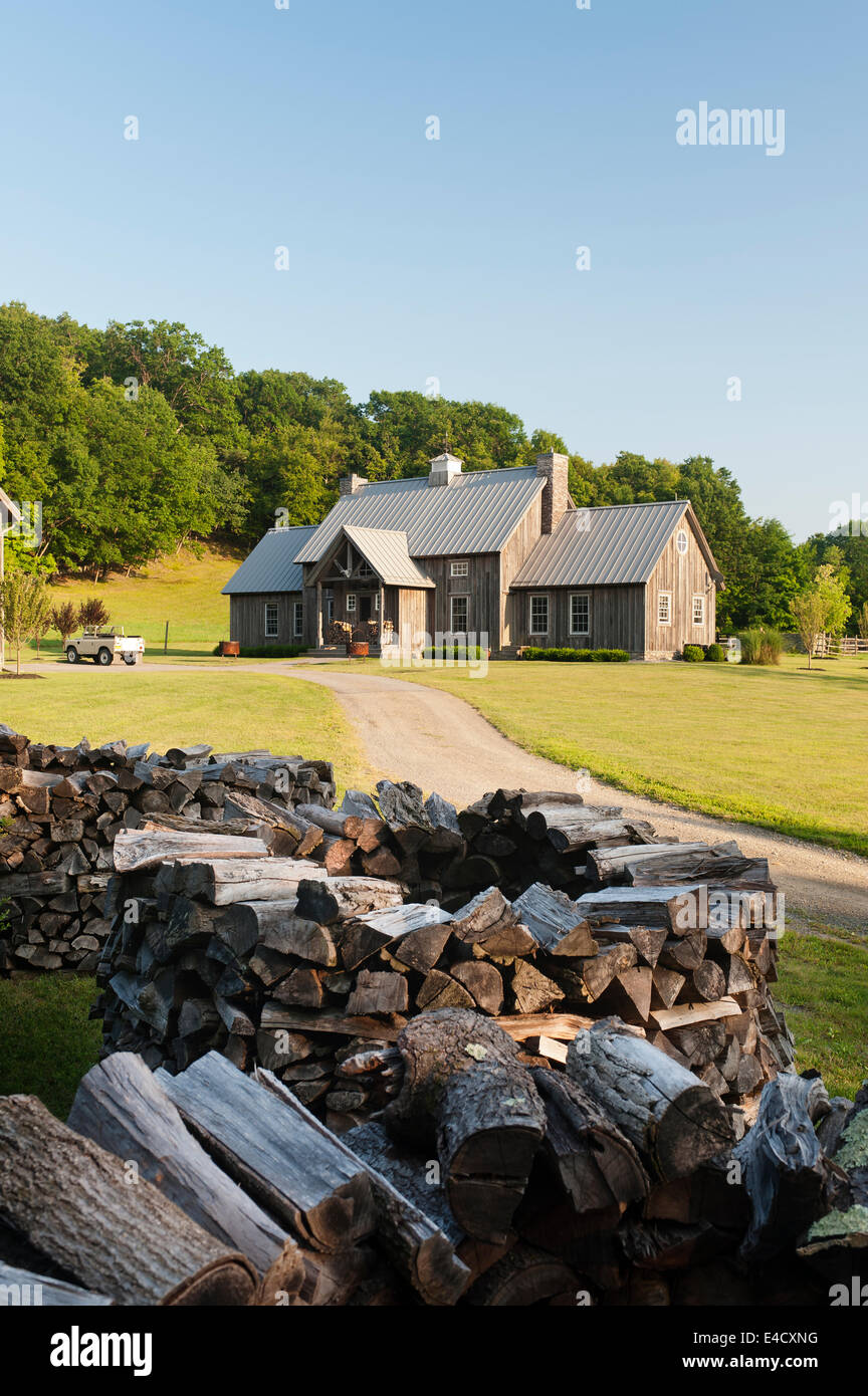 Circular stacks of firewood along driveway to timber framed clad house - Stock Image