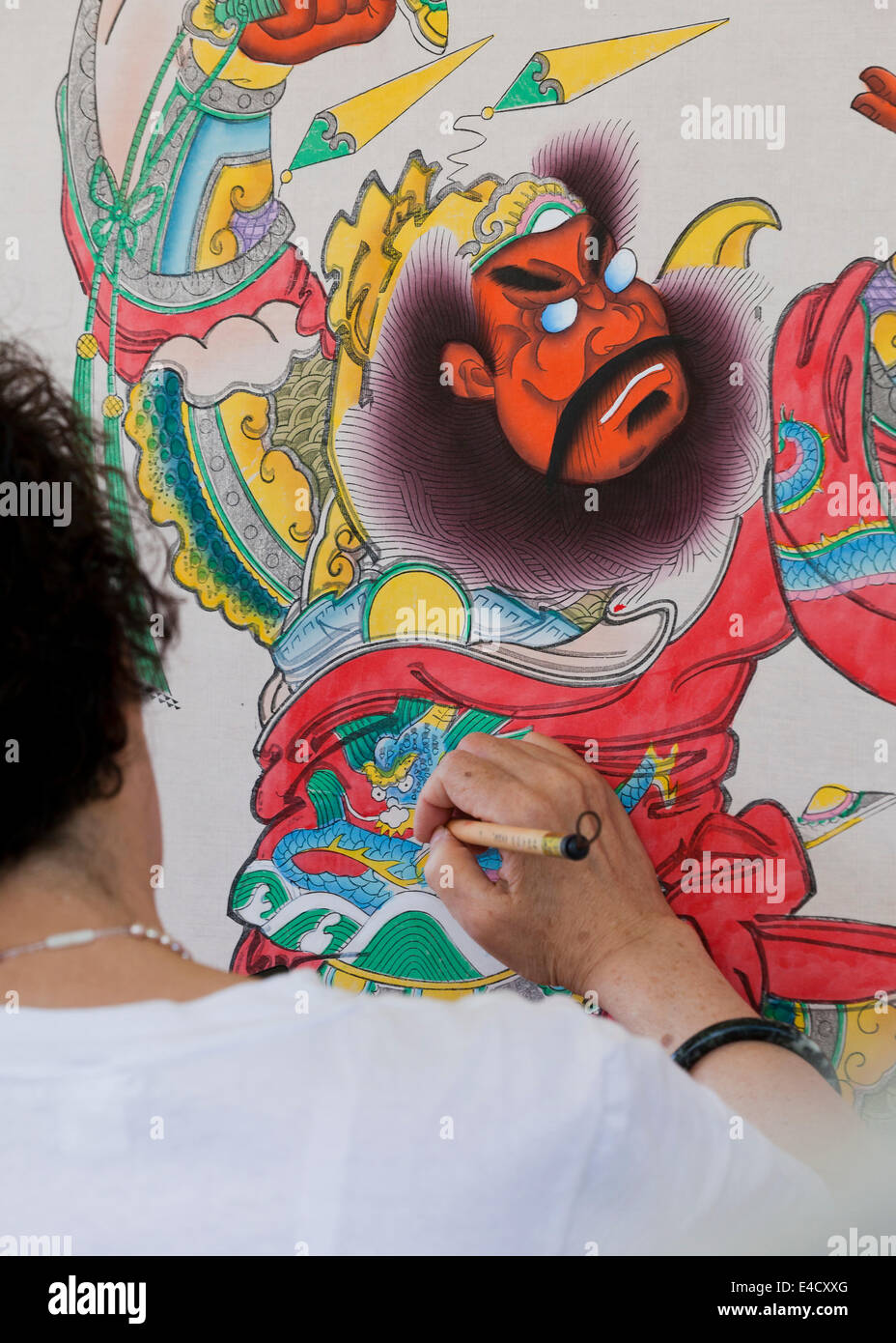 Woman painting Chinese warrior woodblock print - Stock Image
