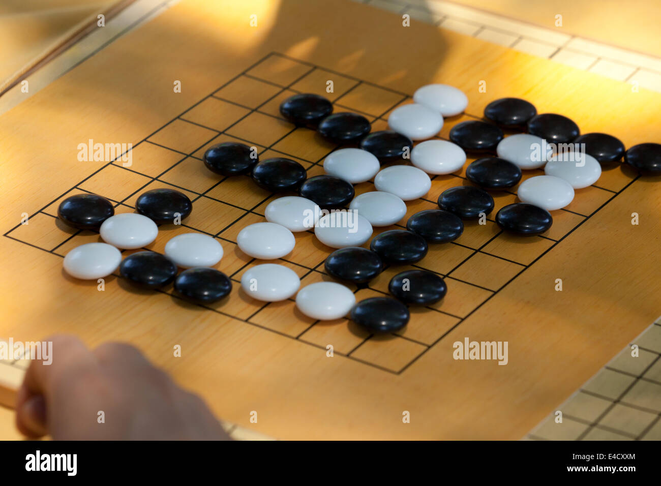 People playing game of Go on beginner board Stock Photo