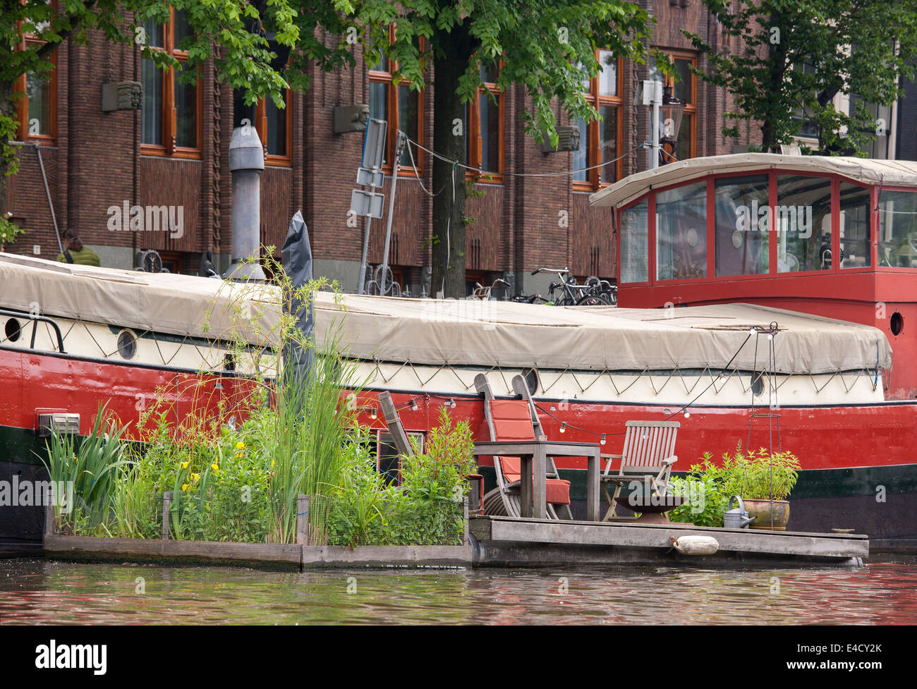 Amsterdam barge house boat with floating garden in the Kromme Waal Canal next to the Amrath Hotel - Stock Image