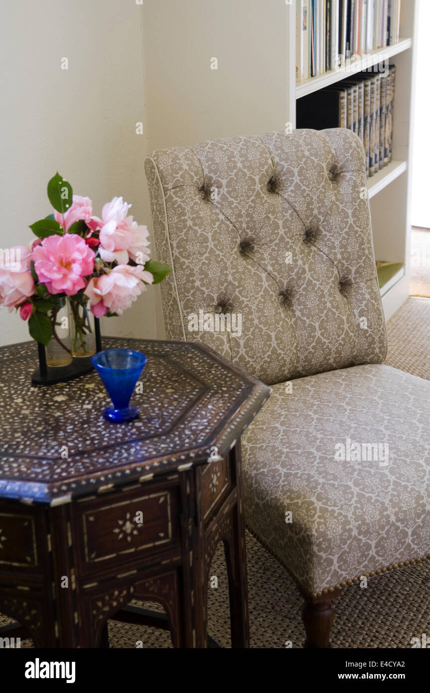 Bone inlaid octagonal occasional table by small buttoned chair - Stock Image