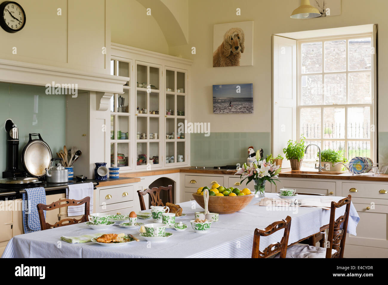 Mouseman chairs by Thompson of Kilburn and place around a dining table in a country style kitchen. - Stock Image