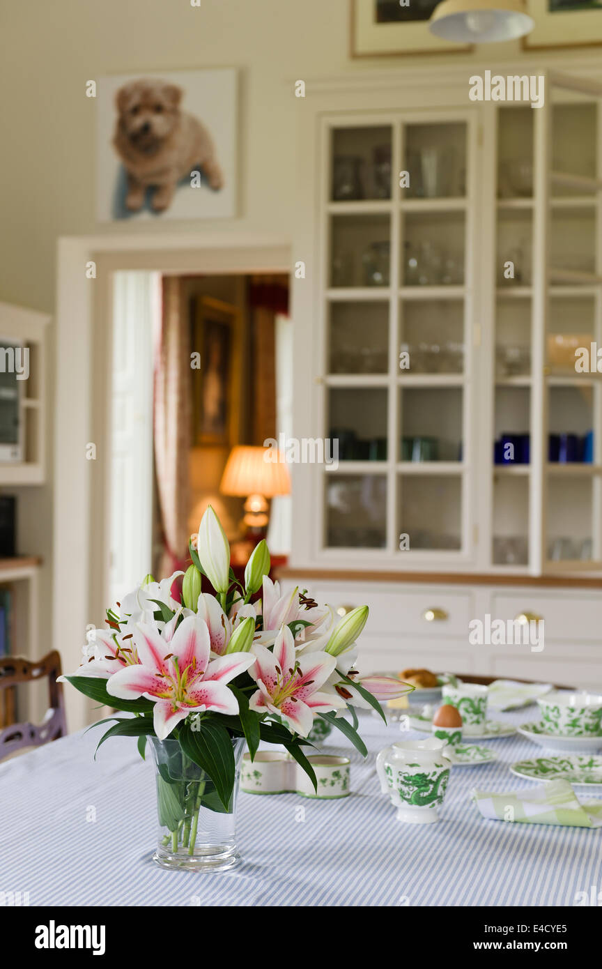 A vase of stargazer lilies adorn a breakfast table laid with Dragon Green crockery by Coalport. - Stock Image