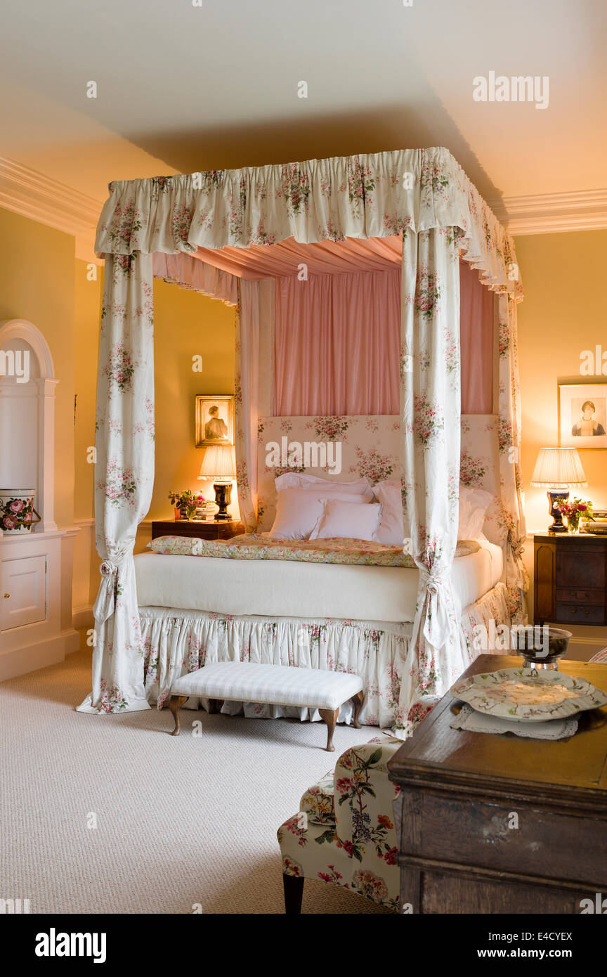 Four poster bed with chintz curtains in olive green bedroom. Paint by Farrow and Ball Stock Photo