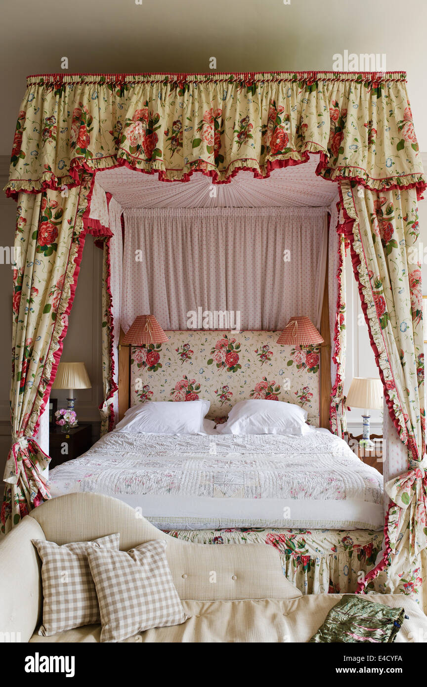 A chaise at the foot of a four poster bed with chintz curtains Stock Photo