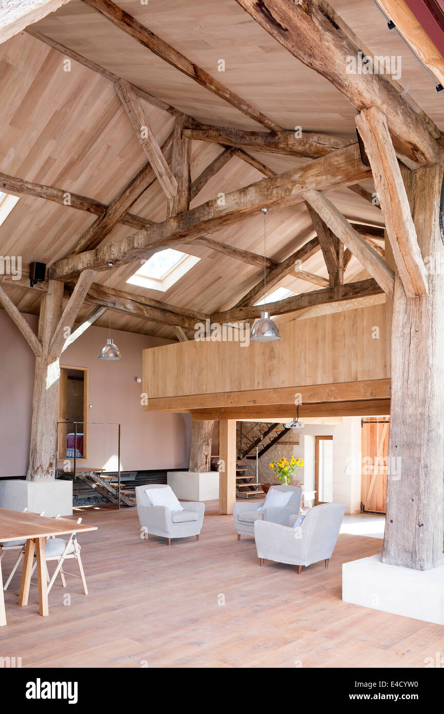 Converted barn with original timber beams, grey armchairs and mezzanine - Stock Image
