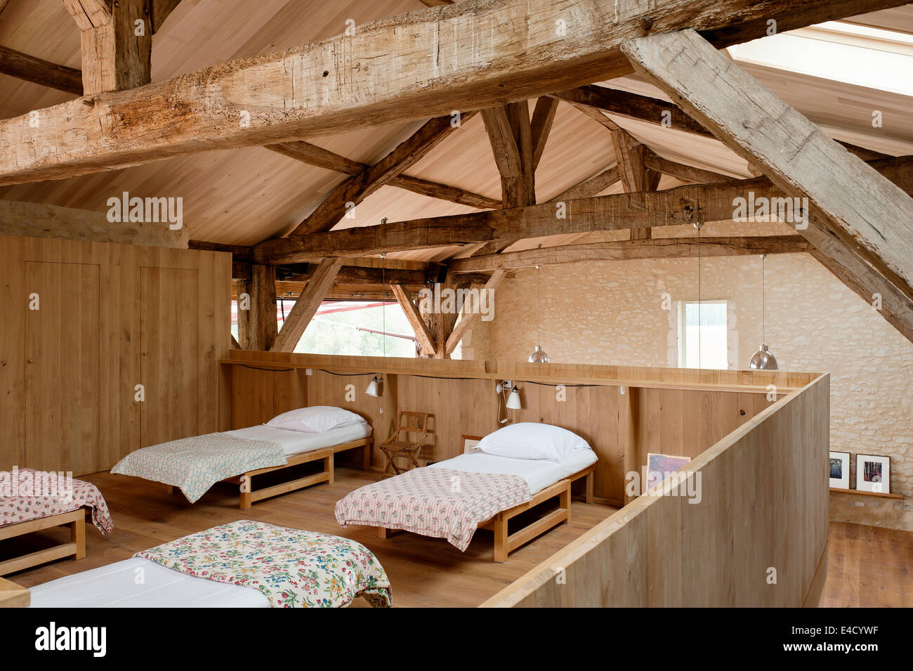 Open plan dormitory accommodation in converted barn with original timber beams - Stock Image