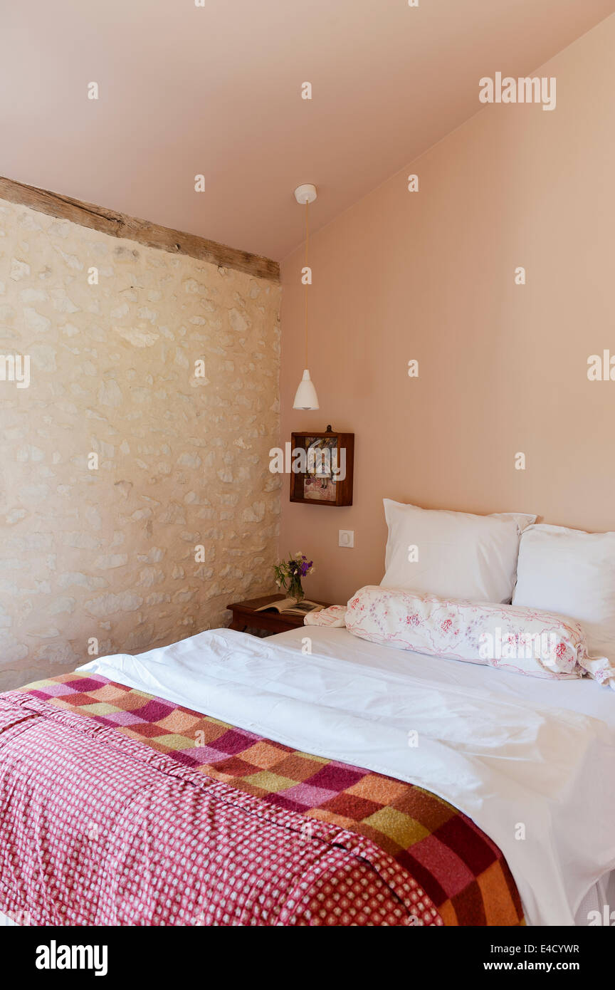 Bedroom with rough stoned wall and vintage bed quilt - Stock Image