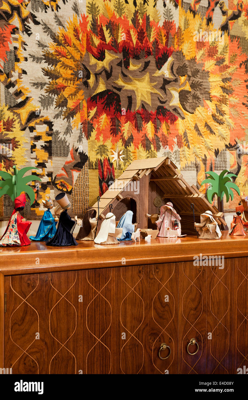 A Jean-Claude Bissery tapestry hung behind a nativity crib scene - Stock Image