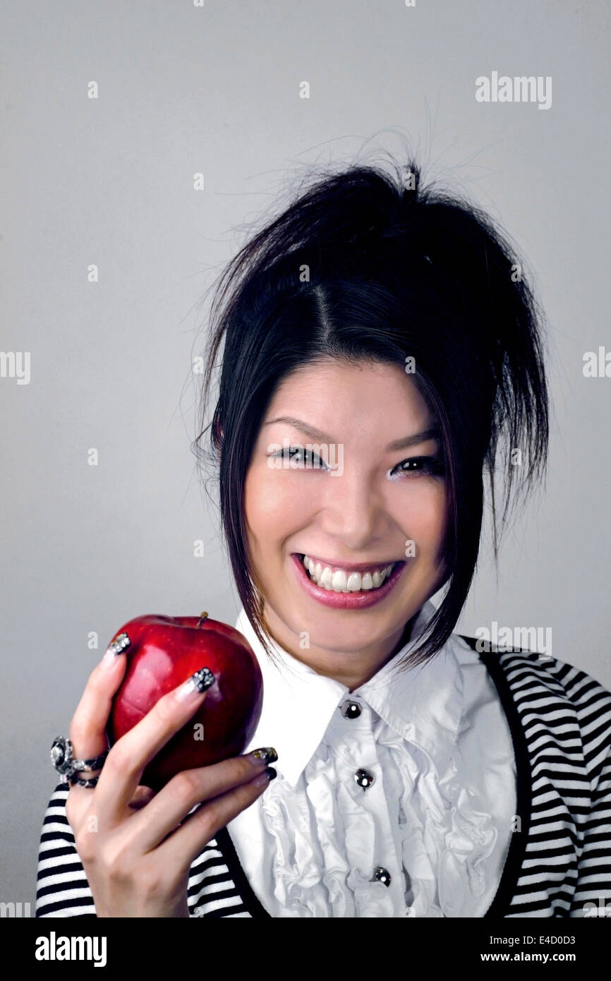 Asian woman holding apple. She is Japanese and was in her early twenties at the time of shoot. - Stock Image