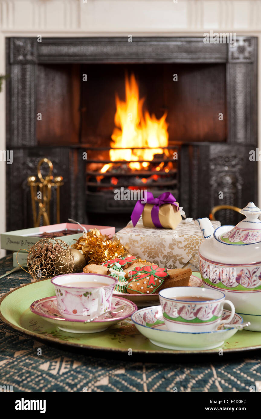 19C hand-painted lustre porcelain tea set tray with christmas biscuits in front of fireplace - Stock Image