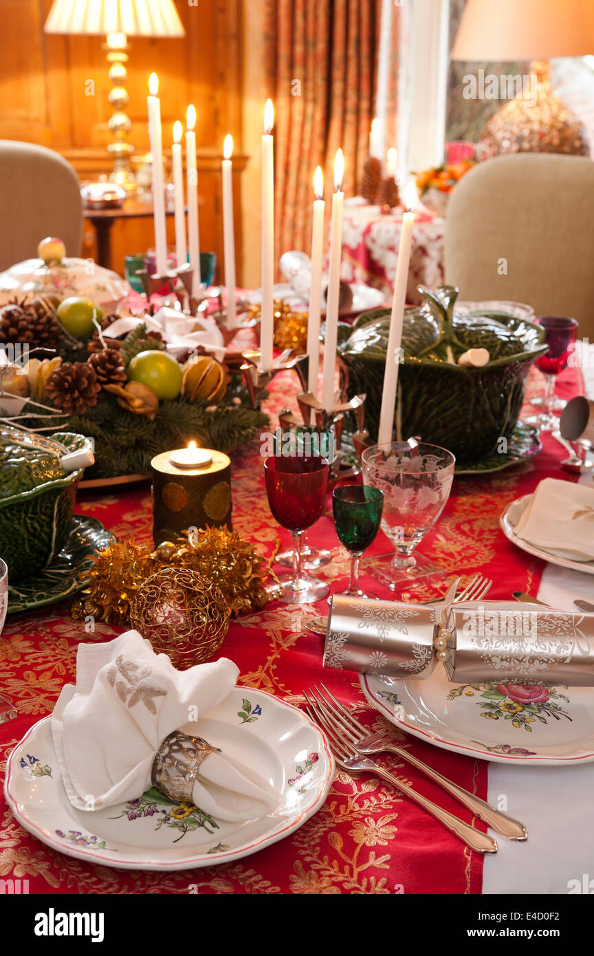 Table laid for christmas dinner with candles and decorations. The tableware is a mix of Luneville Old Strasbourg - Stock Image